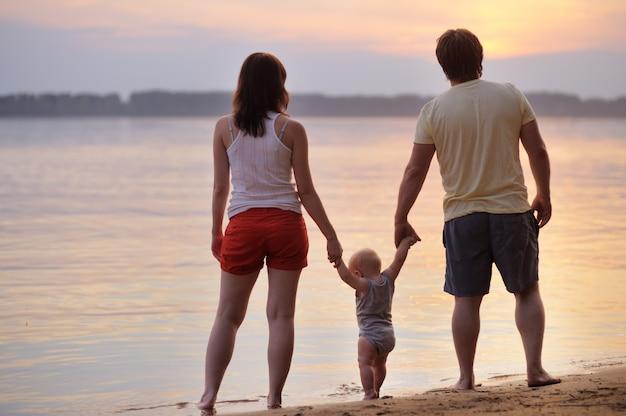 Glückliche dreiköpfige familie am strand bei sonnenuntergang