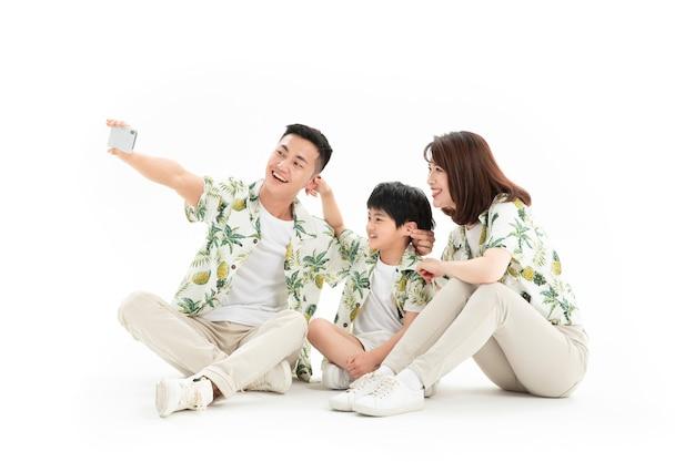 Glückliche dreiköpfige familie, die auf dem boden sitzt und selfie nimmt