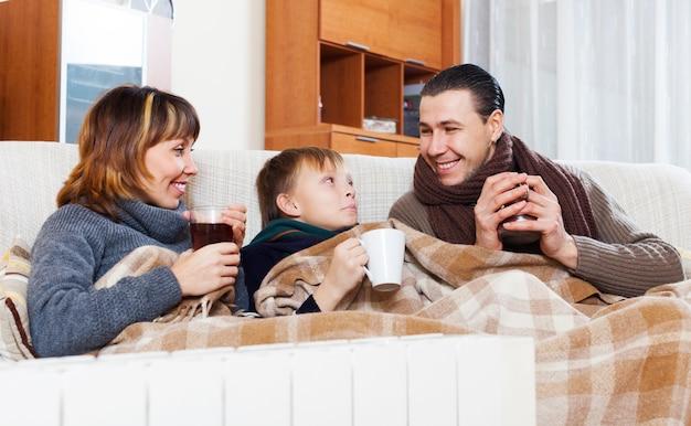 Glückliche dreiköpfige familie, die nahe warmem heizkörper sich wärmt