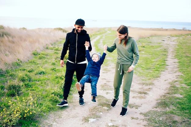 Glückliche dreiköpfige familie, die spaß zusammen im freien hat