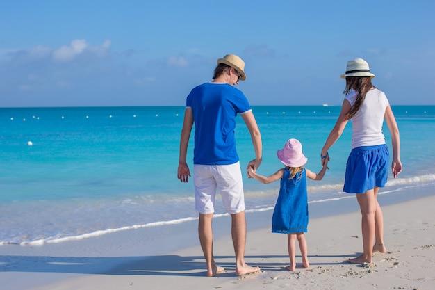 Glückliche dreiköpfige familie, die strandferien genießt