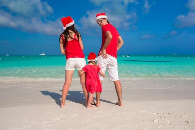 Glückliche dreiköpfige familie in den weihnachtshüten während der tropischen ferien