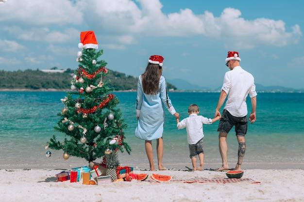 Glückliche dreiköpfige familie in weihnachtshüten während des tropischen urlaubs.