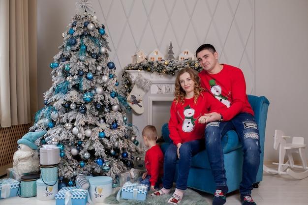 Glückliche dreiköpfige familie, junge mutter erwartet ein neues baby, vater und ihren kleinen sohn nahe geschmücktem weihnachtsbaum.