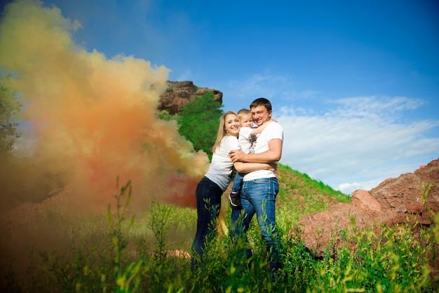 Glückliche dreiköpfige familie mit farbigem rauch im sommer.