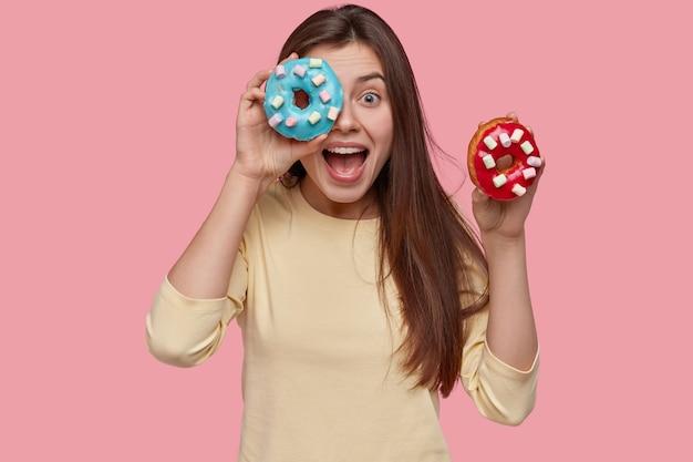 Glückliche dunkelhaarige dame hält zwei leckere donuts, ruft glücklich aus, trägt gelben pullover