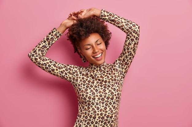 Glückliche dunkelhäutige frau schüttelt körper, hebt hände und tanzt sorglos, trägt leopardenpullover, schließt die augen