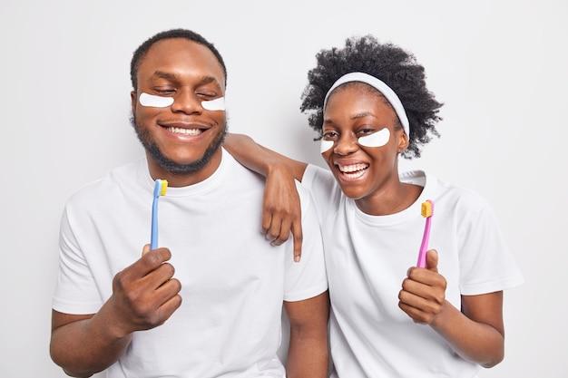 Glückliche dunkelhäutige frau und mann haben spaß bei schönheits- und hygieneverfahren und halten zahnbürsten, um die zähne zu reinigen