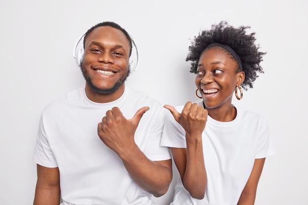 Glückliche dunkelhäutige frau und mann zeigen auf einander lächelnd stehen glücklich nebeneinander