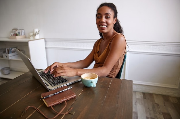 Glückliche dunkelhäutige hübsche frau, die entfernt mit ihrem modernen laptop arbeitet, fröhlich schaut und ihre hände auf tastatur hält
