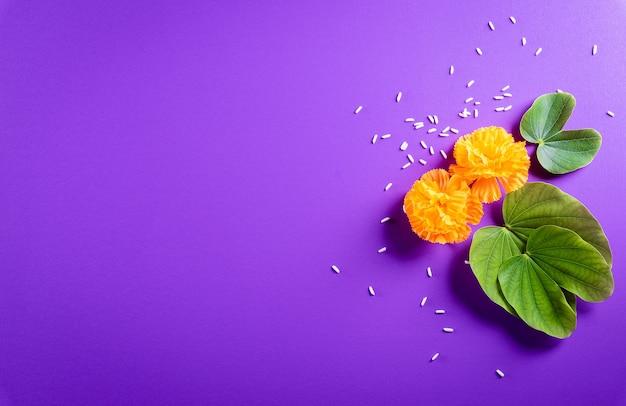 Glückliche dussehra. gelbe blumen, grünes blatt und reis auf lila pastellhintergrund