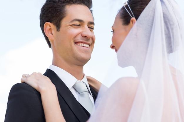 Glückliche eben verheiratete paare gegen himmel