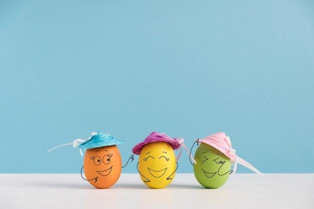 Glückliche eier in hüten lachen. osterferienkonzept mit niedlichen eiern mit lustigen gesichtern. unterschiedliche emotionen und gefühle.