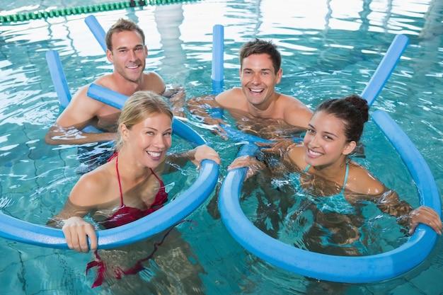 Glückliche eignungsklasse, die aqua aerobic mit schaumrollen tut