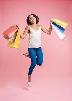 Glückliche einkaufsfrau, die mit bündel einkaufstaschen aufspringt