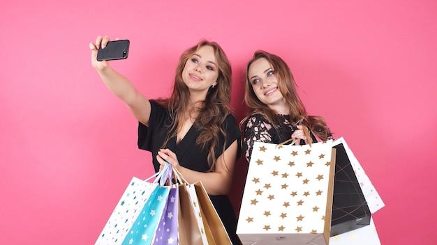 Glückliche einkaufsmädchen nehmen selfies auf einem isolierten hintergrund