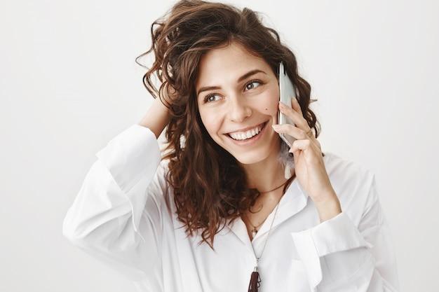 Glückliche elegante frau, die am telefon spricht und lächelt