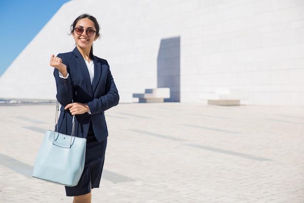 Glückliche elegante geschäftsdame, die zu ihrem büro vorangeht