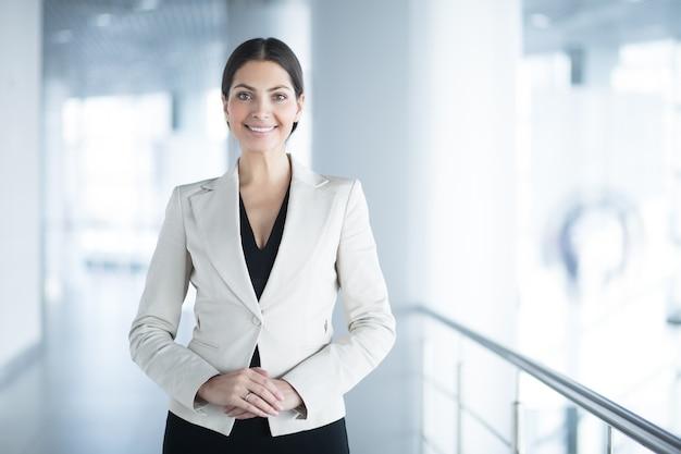 Glückliche elegante geschäftsfrau in der bürohalle