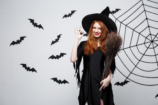 Glückliche elegante hexe genießen, mit besenstiel halloween-party über grauem hintergrund zu spielen.