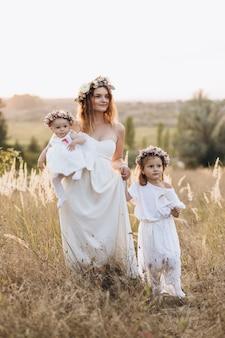 Glückliche elegante mutter und ihre zwei schönen töchter mit blumenkränzen in der natur bei sonnenuntergang