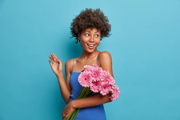 Glückliche elegante nette frau mit blumenstrauß von rosa gerbera-gänseblümchen, bekommt blumen