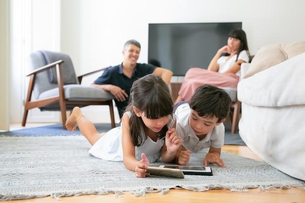 Glückliche eltern beobachten kleine kinder, die auf boden im wohnzimmer liegen und digitale geräte zusammen verwenden.