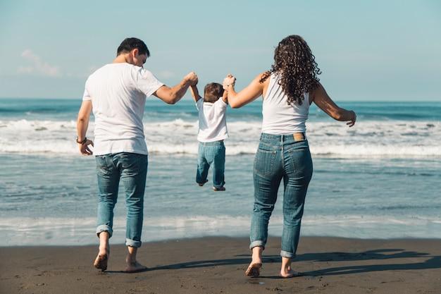 Glückliche eltern, die ihr baby am sonnigen strand werfen