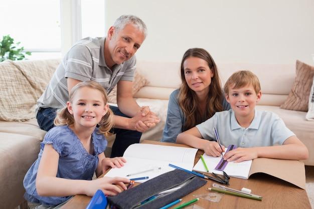 Glückliche eltern, die ihren kindern helfen, ihre hausarbeit zu tun