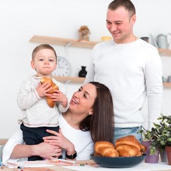Glückliche eltern, die kind mit croissant halten