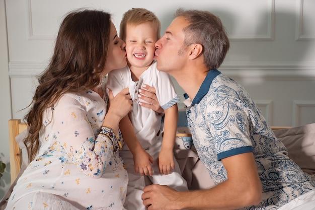 Glückliche eltern, die kleinen jungen im bett küssen, nahaufnahme