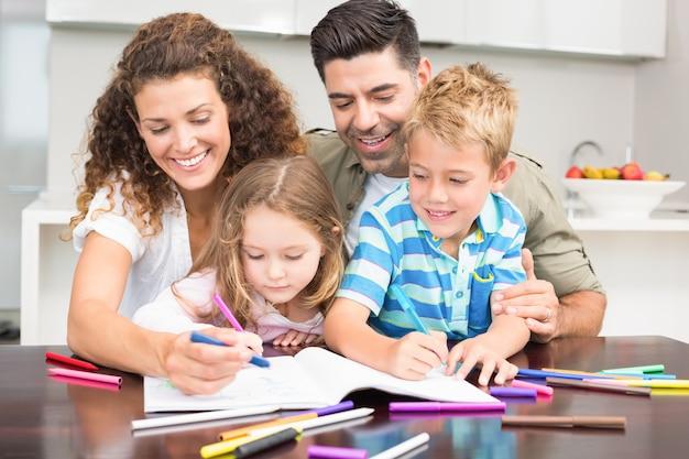 Glückliche eltern, die mit ihren kindern am tisch malen