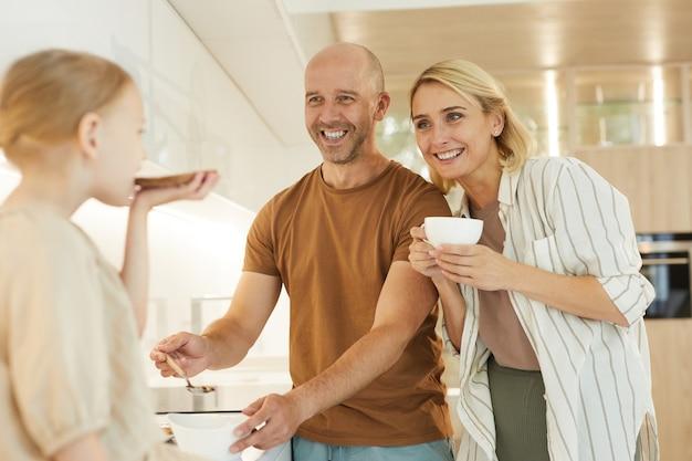 Glückliche eltern, die nettes kleines mädchen betrachten, das gesundes frühstück im modernen kücheninnenraum erleichtert