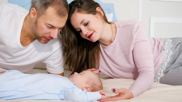 Glückliche eltern, die süßes schlafendes baby im schlafzimmer betrachten