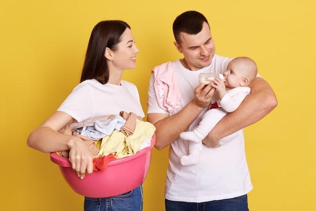 Glückliche eltern, die wäsche tun und neugeborenes mädchen von der flasche füttern, mutter hält basis mit wäsche zum waschen, mama und papa tragen weiße t-shirts, stehen isoliert über gelber wand.