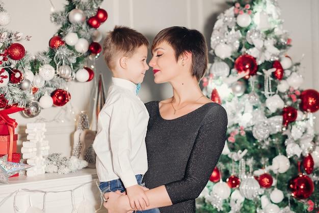 Glückliche eltern, die weihnachtsdekoration auf baum für kleinen sohn zeigen.