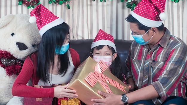 Glückliche eltern, die weihnachtsgeschenk für tochter geben. familie im weihnachtsinnenraum.
