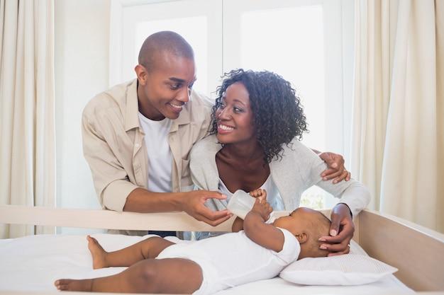 Glückliche eltern, die zu hause ihr baby in seiner krippe in das schlafzimmer einziehen