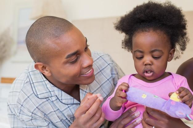 Glückliche eltern, die zusammen mit baby auf bett spielen
