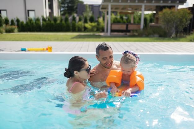 Glückliche eltern. glückliche gutaussehende eltern fühlen sich unglaublich beim schwimmen im pool mit tochter