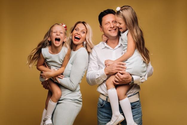 Glückliche eltern halten ihre kinder in ihren armen und lächeln auf gelbem grund. eine emotionale vierköpfige familie.