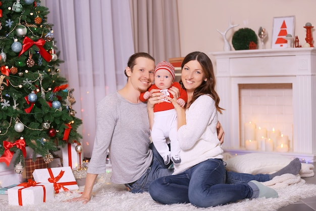 Glückliche eltern mit baby in der nähe von weihnachtsbaum auf dem boden im dekorierten raum