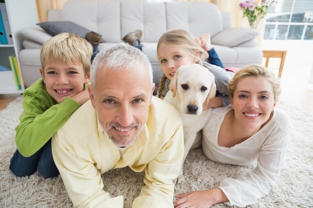 Glückliche eltern mit ihren kindern und welpen auf dem boden