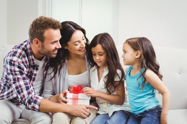 Glückliche eltern mit ihren töchtern, die eine geschenkbox halten