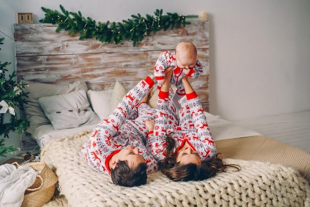 Glückliche eltern mit ihrer kleinen tochter in der feiertagskleidung mit den druckrotwild und schneeflocken, die spaß auf dem bett im gemütlichen raum mit einem weihnachtsbaum haben
