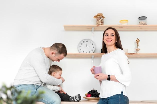 Glückliche eltern mit kind in der küche