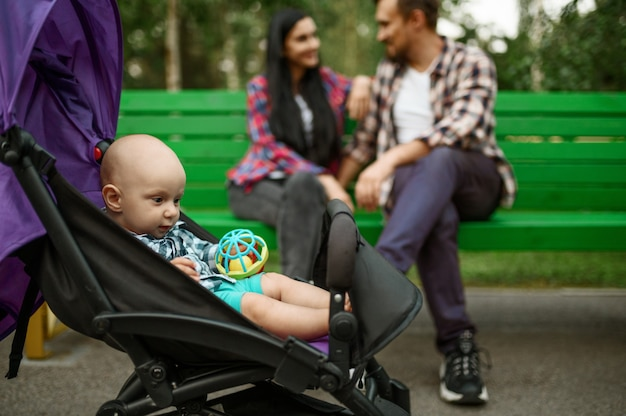 Glückliche eltern mit kleinen babyfreuden auf bank im sommerpark
