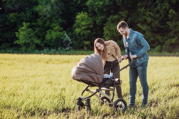 Glückliche eltern mit liebe und zärtlichkeit schauen ihr kind an, das in einem kinderwagen liegt