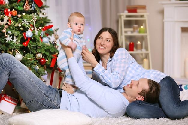 Glückliche eltern spielen mit baby auf dem boden im dekorierten weihnachtszimmer