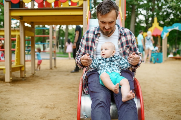 Glückliche eltern spielen mit kleinem baby auf spielplatz im sommerpark